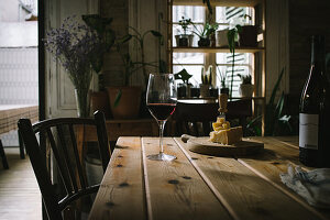 Rotweinflasche und -glas mit Käseplatte auf rustikalem Holztisch