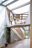 Offener Wohnraum mit Holztreppe im Architektenhaus