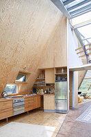 Einbauküche mit schräger, holzverkleideter Wand