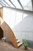 Wooden staircase next to concrete wall in architect-designed house