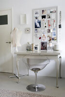 Transparent chair at console table below framed collage