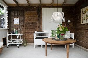 Rustikales Wohnzimmer mit Holzwänden und weißem Boden