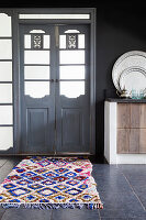 Colourful, diamond-patterned rug in front or Oriental wooden door