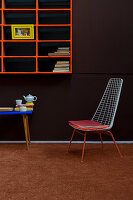Metal chair below orange shelves on brown wall