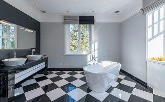 Free-standing bathtub and black-and-white chequered floor in modern bathroom