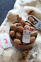 Bowl of nuts and paper cat on woollen blanket