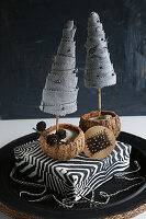 Two miniature fabric fir trees on zebra-patterned box against black background