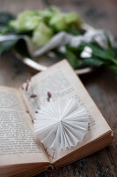 Small white paper rosette used as bookmark