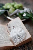 Kleine weiße Papierrosette als Lesezeichen