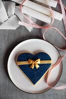 Großes Herzplätzchen mit blauem Fondantüberzug und goldener Schleife