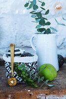 Krug mit Eukalyptuszweigen, Stoffbeutel mit Weihnachtskugeln und grüner Apfel