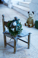 Christmas wreath on child's chair with teddy bear in background