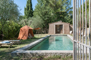 Tent used as sun shade next to swimming pool in Mediterranean garden