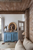 Bric-a-brac on blue sideboard and bed with wooden canopy in bedroom