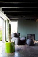 Kaktus und Designersessel im Wohnzimmer mit Balkendecke