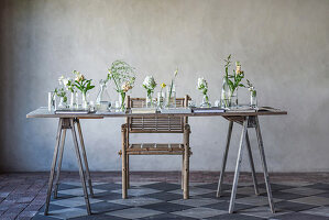 Flowers in various glass containers on rustic wooden table
