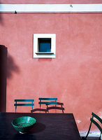 Tisch mit Stühlen vor rosa Fassade mit kleinem Fenster