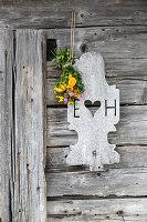 Blumenstrauß mit echten Blumen und mit Papierblüten über rustikaler Holztür