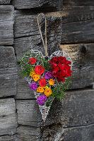 Dekoherz aus Weidengeflecht mit echten Geranien und bunten Papierblüten