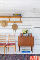 Chairs and cabinet against board wall in rustic wooden house