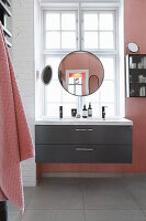 Round mirror above sink and in front of lattice window in pink bathroom