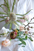 Making a spring bouquet of banksia, tulips, ranunculus, carnations, freesias, branches of magnolia and eucalyptus
