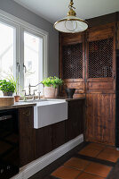 Belfast sink in rustic country-house kitchen with dark wooden cabinets