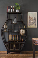 Black, vase-shaped shelving unit against dark grey wall in dining room