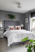 Gepolstertes Betthaupt im eleganten Schlafzimmer in Grau und Weiß