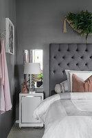 Nachttisch und Spiegel neben dem Bett im Schlafzimmer in Grau