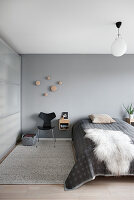 Sheepskin rug on bed in simple bedroom in shades of grey