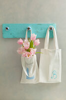 Hand-sewn cloth bags hung from DIY pegs made from wooden board and furniture knobs