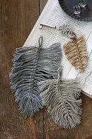 Makramee-Federn aus Wolle als Schlüsselanhänger auf altem Buch