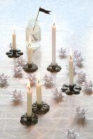 Weihnachtsdekoration mit Mini-Kerzenständern und weissen Fröbelsternen
