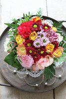 Blumenstrauss mit gelben und rosa Rosen auf Holztablett mit Perlengirlande