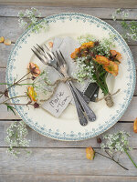 Posy of geums and cow parsley decorating plate