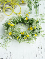 Wreath of cow parsley and buttercups on plate as table decoration for 60th birthday