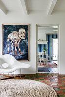 Designer chair on terracotta floor tiles and modern artwork on wall