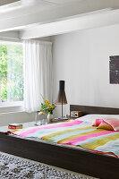 Doppelbett mit gestreifter Decke vor Fenster in hellem Schlafzimmer