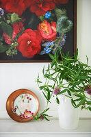 Vase mit Blätterzweig auf Sideboard