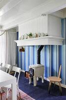 Kaminofen vor blau gestreifter Tapete im Esszimmer