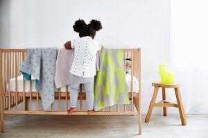 Kleines Mädchen steht auf dem Gitterbett