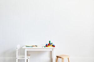 Weißer Kindertisch mit bunten Malstiften und Bauklötzen, weißer Stuhl und Hocker