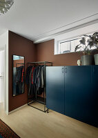 Clothes rail between tall, blue sideboard and mirror in bedroom with brown walls