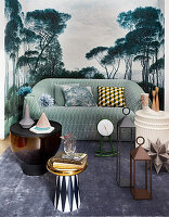 Coffee table, lanterns and green sofa against mural wallpaper with landscape motif