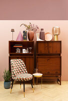 Vases on retro sideboard, easy chair and side table
