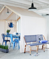 Garden bench and house-shaped tent over table and garden chairs in loft apartment