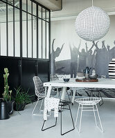 White metal table and wire chairs in black-and-white dining area of loft apartment