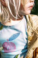 Child wearing T-shirt with printed apple motif