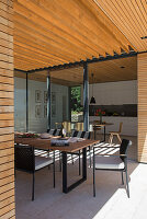 Dining table on roofed terrace of modern, architect-designed house